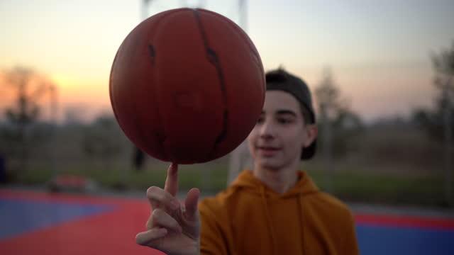 teenage boy spinning basketball ball on sports court - teenage boys stock videos & royalty-free footage