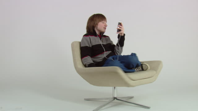 WS ZI CU Teenage boy spinning in chair and nodding his head to music while holding mp3 player / New York, USA