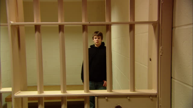 ms teenage boy standing in prison cell, looking at camera as door closes, then opens/ new jersey - männlicher teenager allein stock-videos und b-roll-filmmaterial