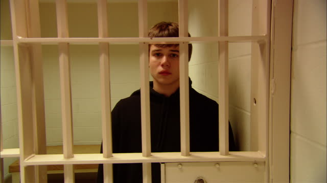 ms teenage boy standing in prison cell, looking at camera as door opens, then closes/ new jersey - security bar stock videos and b-roll footage