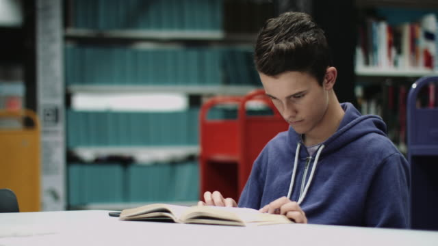 teenage boy studying book in library - un ragazzo adolescente video stock e b–roll