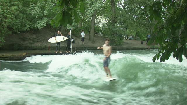 MS Teenage boy surfing on Eisbach river in Englischer Garten (English Garden), Munich, Bavaria, Germany
