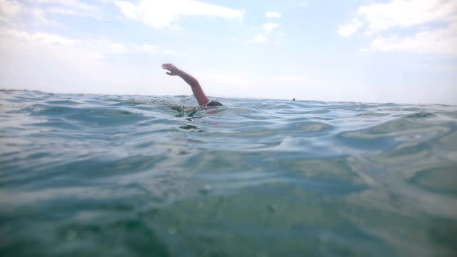 teenage boy swimming in the ocean doing breastwork - galleggiare sull'acqua video stock e b–roll