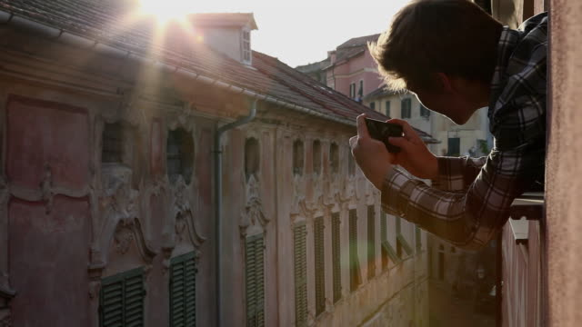 teenage boy takes picture from window in medieval quarter - one teenage boy only stock videos and b-roll footage