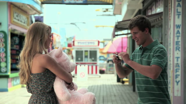 Teenage boy taking picture of girlfriend with teddy bear
