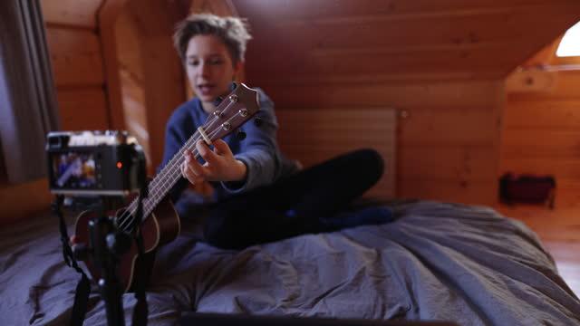 teenage boy teaching how to play ukulele - filming stock videos & royalty-free footage