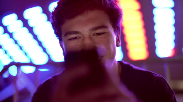stockvideo's en b-roll-footage met cu teenage boy texting at a carnival at night - handheld