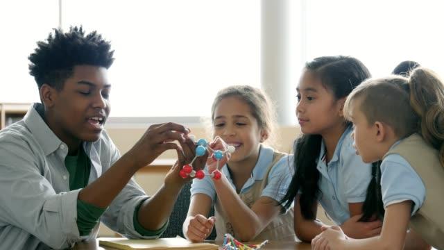 teenage boy tutors elementary students - atom stock videos & royalty-free footage