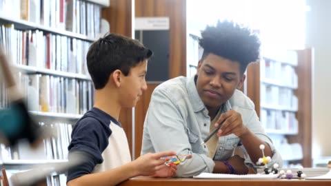 teenage boy tutors middle school student - volunteer stock videos & royalty-free footage