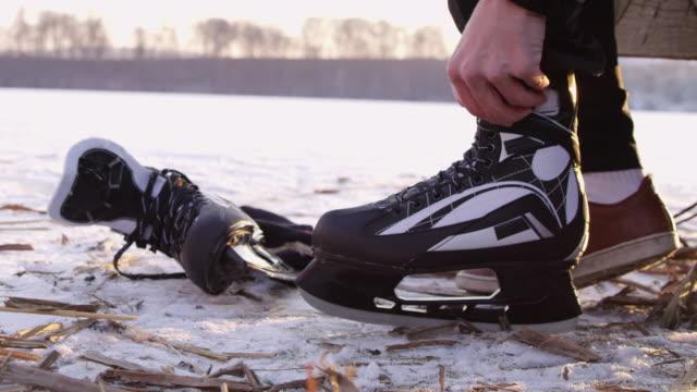 4K Teenage boy tying ice skate shoelace on frozen lake, slow motion