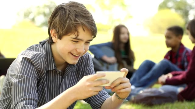 teenage boy uses cell phone in park or school campus. - teenager stock videos & royalty-free footage