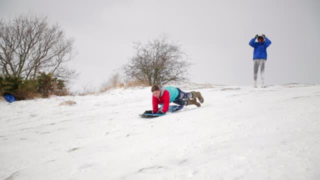 Teenage Boy Using a Body Board Down a Hill