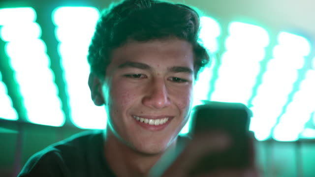 vidéos et rushes de cu teenage boy using his phone at a carnival at night - jeunes garçons
