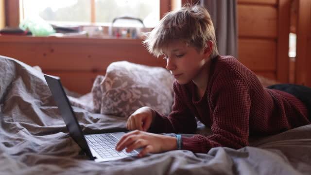stockvideo's en b-roll-footage met tiener die laptop in bed met behulp van - 10 11 jaar