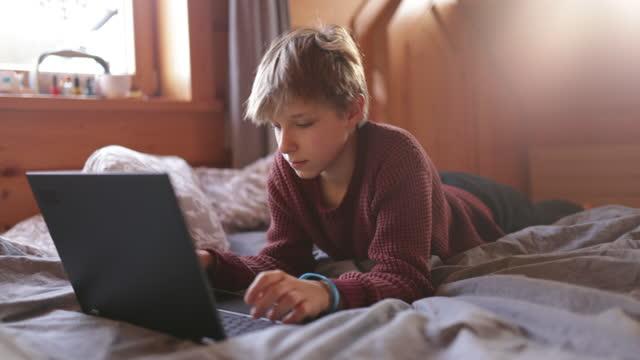 tonårspojke som använder bärbar dator i sängen - sovrum bildbanksvideor och videomaterial från bakom kulisserna