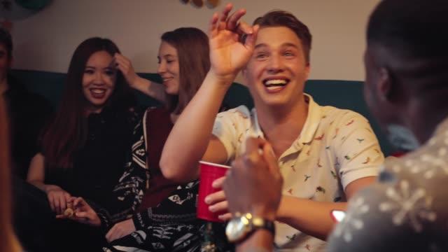 teenager mit telefon beim sitzen mit freunden - männlicher teenager stock-videos und b-roll-filmmaterial