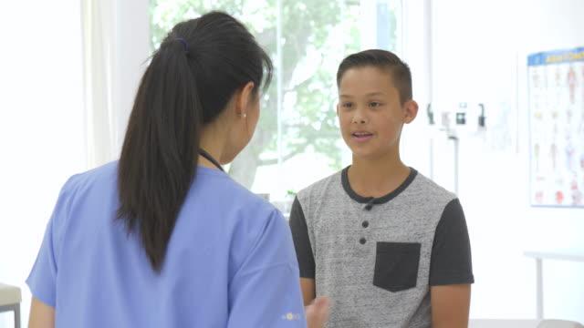 十代の少年が医者を訪ねる - 小児科医点の映像素材/bロール