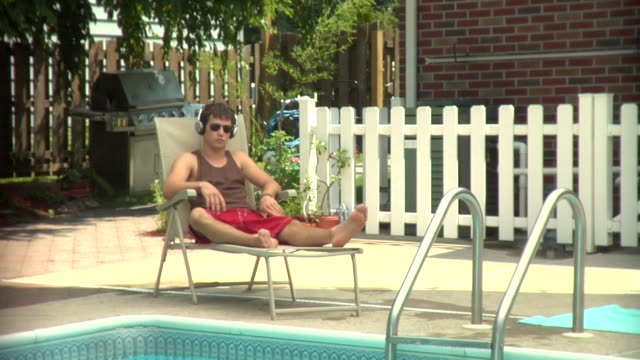 ms, teenage boy (16-17) wearing headphones listening music on poolside, middlesex, new jersey, usa - one teenage boy only stock videos & royalty-free footage