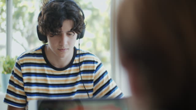 cu teenage boy wearing headphones while using a computer at home - using computer stock videos & royalty-free footage
