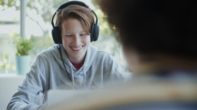 cu teenage boy wearing headphones while using a computer at home - using laptop stock videos & royalty-free footage