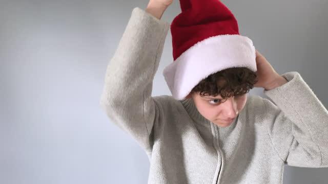 teenage boy wears santa hat in minimalist christmas video in front of gray background - antler stock videos & royalty-free footage