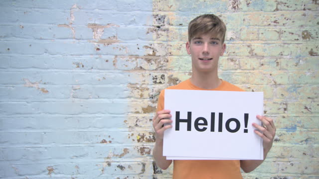 Teenage boy with greeting on signs