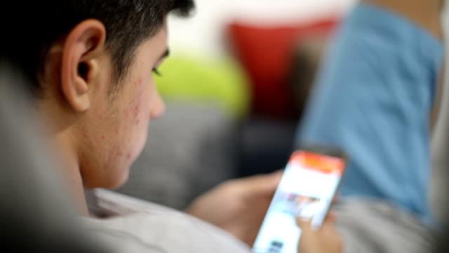 Tiener met telefoon thuis liggend op een bank