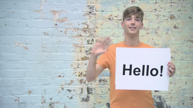 teenage boy with signs reading hello and bye - welcome segnale inglese video stock e b–roll