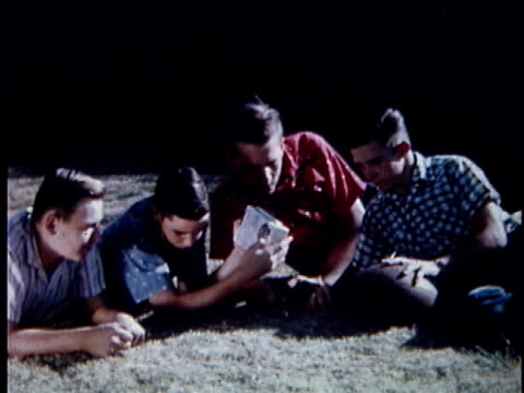 vidéos et rushes de ms teenage boys and young men listening to radio and lying on grass, then they cheer / usa - écouter