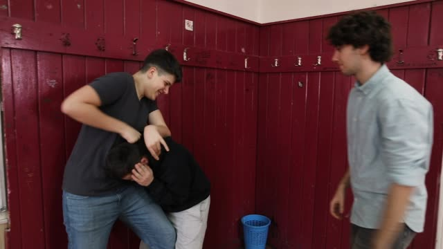 Teenage boys bullying their classmate in a high school classroom while girls taking shots with camera