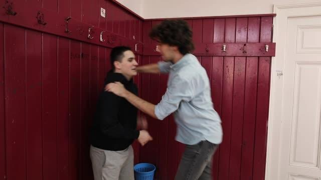 stockvideo's en b-roll-footage met tiener jongens pesten hun klasgenoot in een middelbare schoolklas terwijl meisjes het nemen van foto's met camera - slagen school