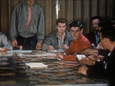 1954 teenage boys dropping ballots in box while passing it around conference table / USA