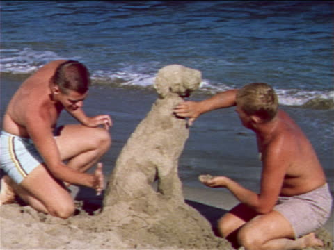 stockvideo's en b-roll-footage met 1959 2 teenage boys in bathing suits building sand-dog on beach / industrial - prelinger archief