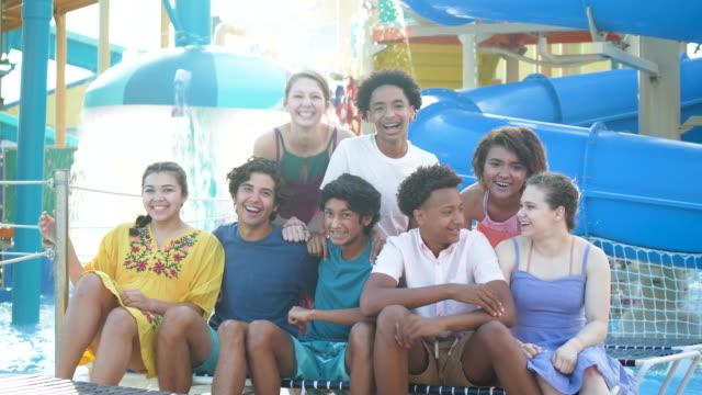teenage jungen von teenager-mädchen im wasserpark begleitet - multi ethnic group stock-videos und b-roll-filmmaterial