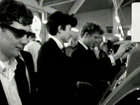 teenage boys play on slot machines in an amusement arcade - fruit machine stock videos & royalty-free footage