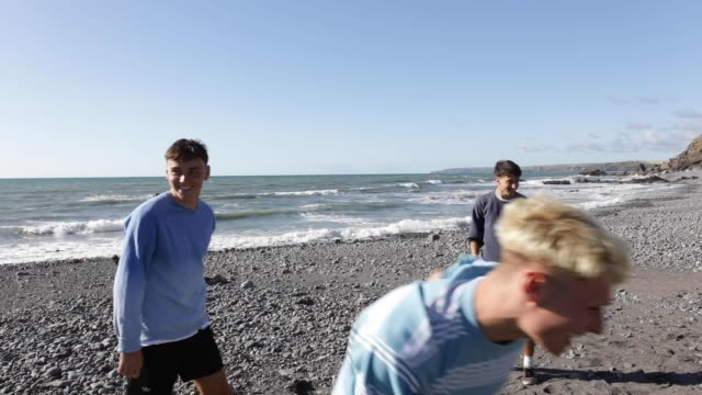 teenage boys playing football on an empty beach. - eco tourism stock videos & royalty-free footage