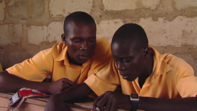 MS Teenage boys reading aloud sitting in classroom, Tamale, Ghana