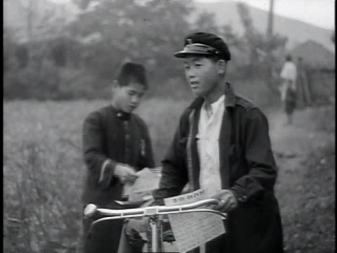 vidéos et rushes de ms teenage boys with bicycles and pamphlets reading / korea - 1953