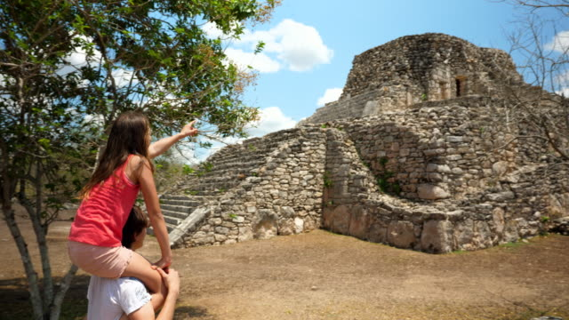 ms teenage brother giving younger sister ride on shoulders during visit to mayapan ruins during family vacation - 肩に乗せる点の映像素材/bロール