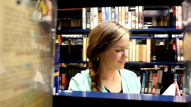 teenage caucasian female high school home school student searches for book at local public library - high school student stock videos and b-roll footage