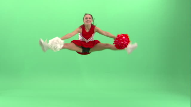 ws, teenage (16-17) cheerleader jumping in studio - cheerleader stock videos and b-roll footage
