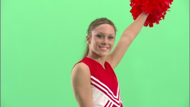 cu, teenage (16-17) cheerleader shaking pom poms in studio, portrait - pom pom stock videos & royalty-free footage