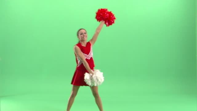 ws, teenage (16-17) cheerleader shaking pom poms in studio - cheerleader stock videos and b-roll footage