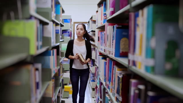 stockvideo's en b-roll-footage met teenage kiezen van een boek in de bibliotheek. - boekwinkel