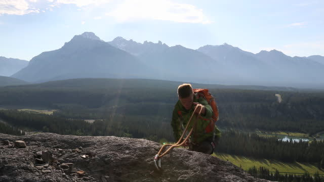 teenage climber ascends to rock ledge, mtns below - one teenage boy only stock videos & royalty-free footage