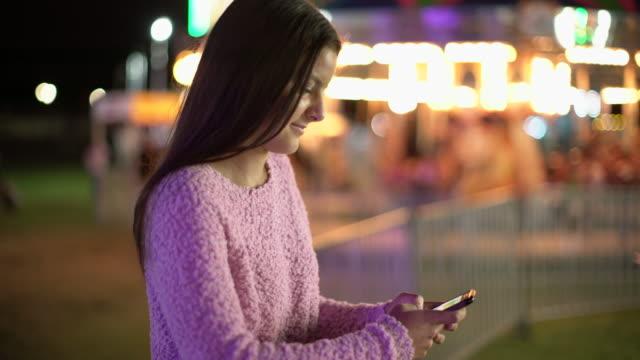 Teenage couple at a carnival at night