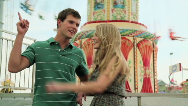 teenage couple at fun fair, girl dragging boyfriend away - teenage couple stock videos & royalty-free footage