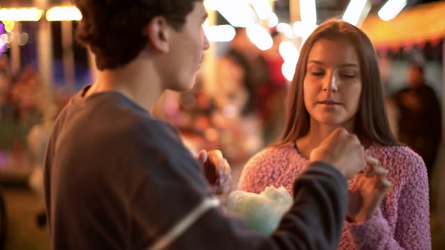 vidéos et rushes de ms teenage couple eating cotton candy at a carnival at night - couple d'adolescents