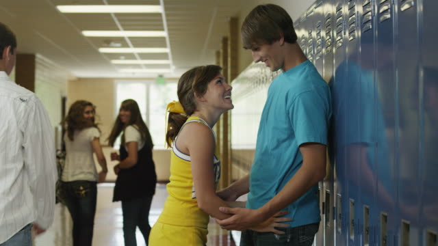 vidéos et rushes de ms teenage couple (14-17) embracing in school corridor / spanish fork city, utah, usa - couple d'adolescents