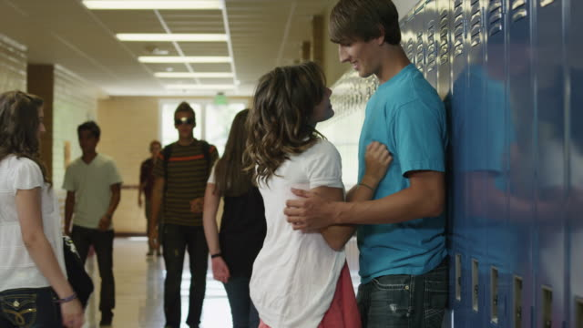 ms teenage couple (14-17) embracing in school corridor / spanish fork city, utah, usa - teenagerpaar stock-videos und b-roll-filmmaterial